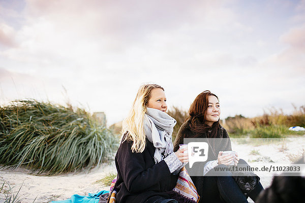 Friends looking away while holding coffee mugs on beach against sky
