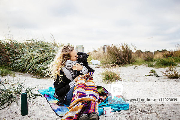 Young woman kissing dog while sitting on beach against sky