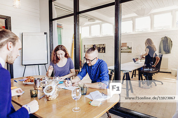 Creative business people working at table in board room