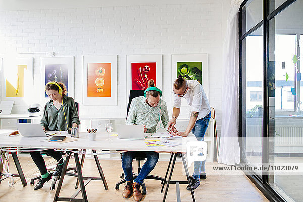 Team of creative business people working at table in office