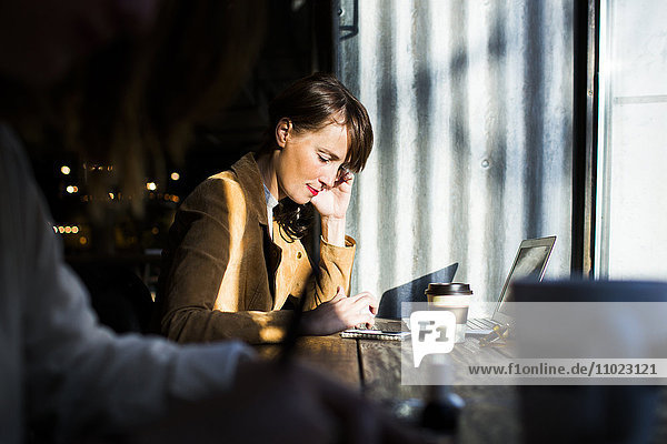Side view of woman using smart phone while sitting at cafe table