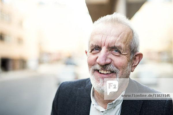 Close-up portrait of senior businessman smiling outdoors