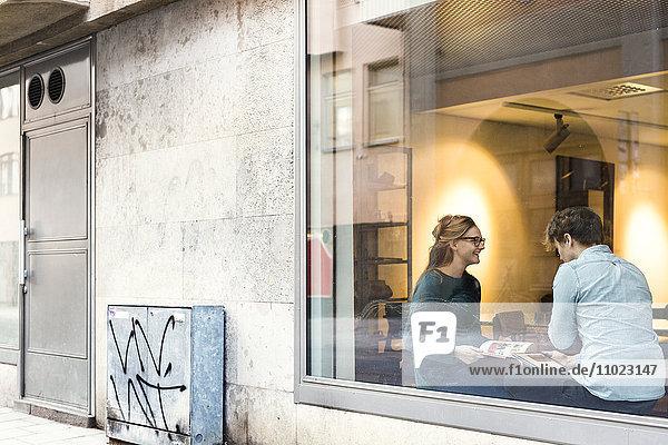 Businessman and businesswoman seen through glass window of office