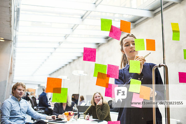 Young businesswoman giving presentation on sticky notes to colleagues in office