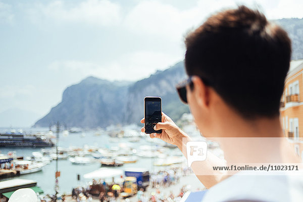Young man photographing through smart phone at Marina Grande against sky