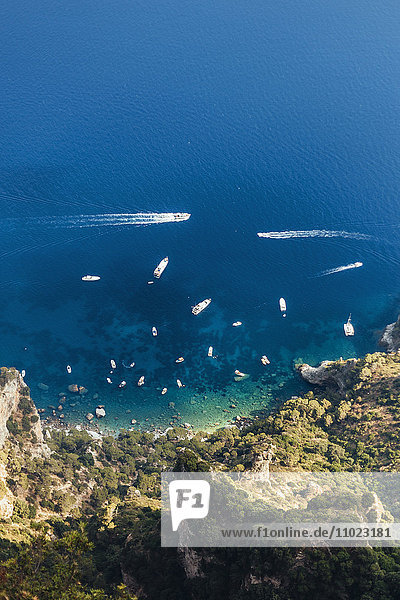 Aerial view of boats moving on sea by mountain