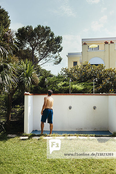 Rear view of man standing under shower in yard