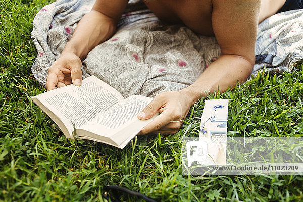 Man reading book while relaxing on grassy field