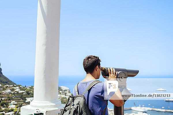 Man looking through telescope at Amalfi Coast against sky