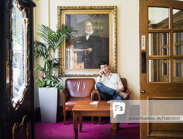 Man using mobile phone while sitting on armchair at hotel lobby