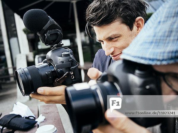 Close-up of photographer using digital cameras outdoors