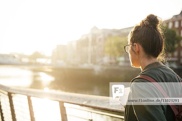 Rear view of woman standing by river on sunny day