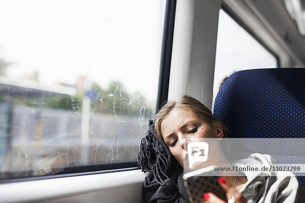 Businesswoman using smart phone while travelling in train