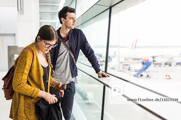 Business people looking through glass window at airport