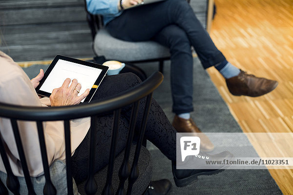 Low section of businesswoman using digital tablet during meeting at hotel lobby
