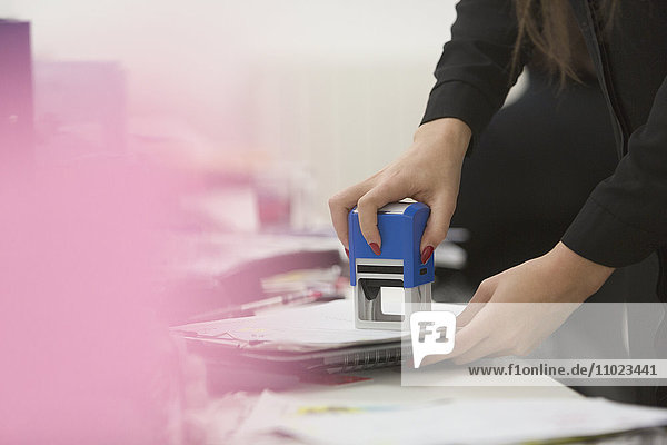 Businesswoman using stamp on paperwork in office