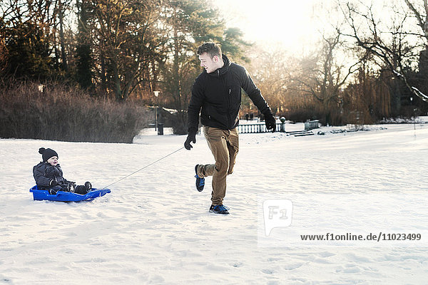 Young father tobogganing baby boy on snowy field