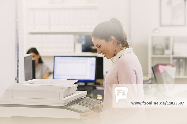 Smiling businesswoman making copies at copier in office