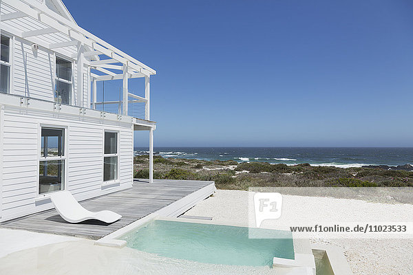 Beach house soaking pool and deck overlooking ocean under sunny blue sky