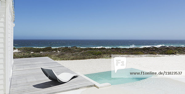Soaking pool and modern lounge chair with ocean view under sunny blue sky