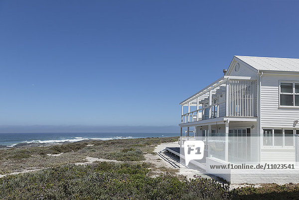 White beach house with ocean view under sunny blue sky