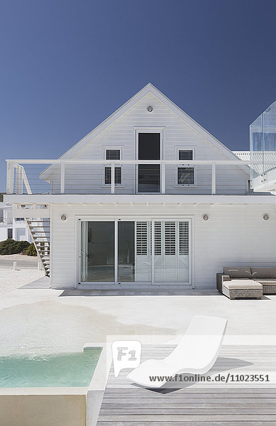 White house with swimming pool and modern lounge chair under sunny blue sky