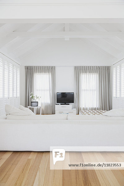 White living room with vaulted wood beam ceiling in home showcase interior