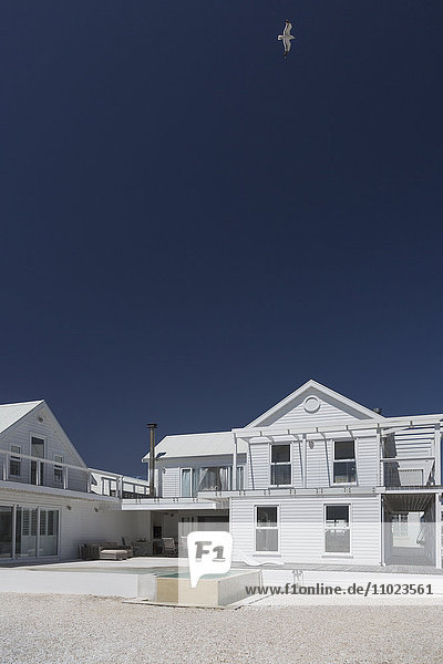 White house and swimming pool under sunny blue sky