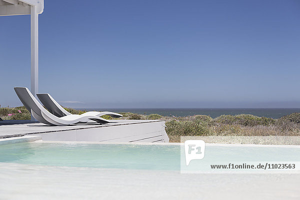 Swimming pool and modern lounge chairs overlooking ocean view under sunny blue sky