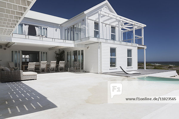 White beach house with sunny swimming pool