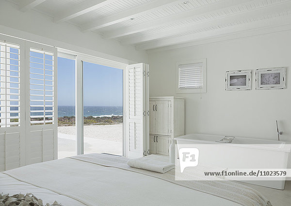 White hotel room with en suite soaking tub and ocean view