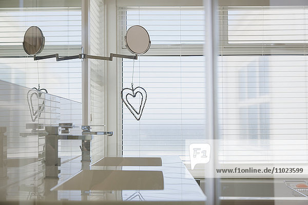 Heart-shape decoration hanging from mirror in modern white home showcase bathroom