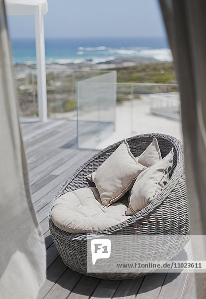 Wicker seat with cushions on sunny beach house deck with ocean view