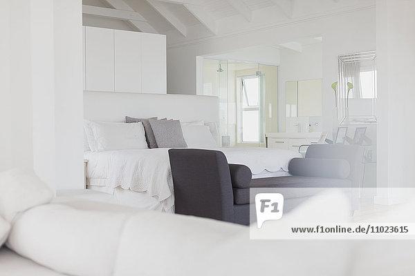 White bedroom with en suite bathroom in home showcase interior