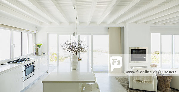 White kitchen with wood beam ceilings in home showcase interior
