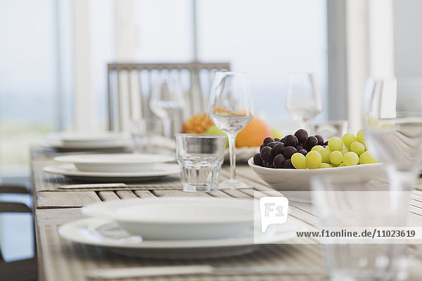 Placesettings and grapes on dining table