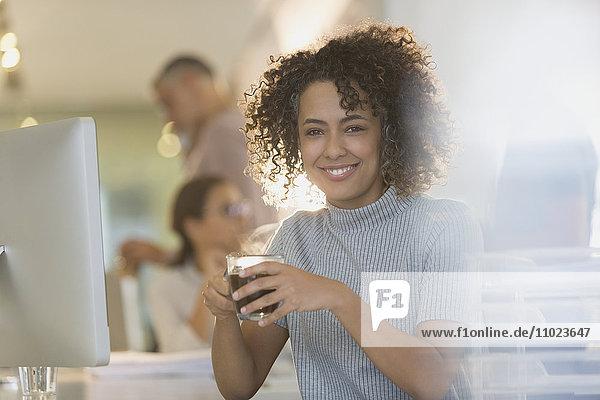 Portrait smiling businesswoman drinking coffee in office