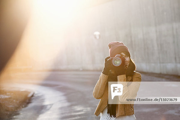 Woman wearing jacket photographing with camera outdoors