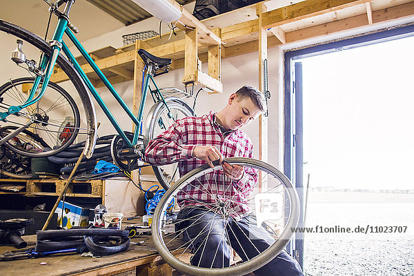 Man repairing bicycle tire while sitting by doorway in workshop