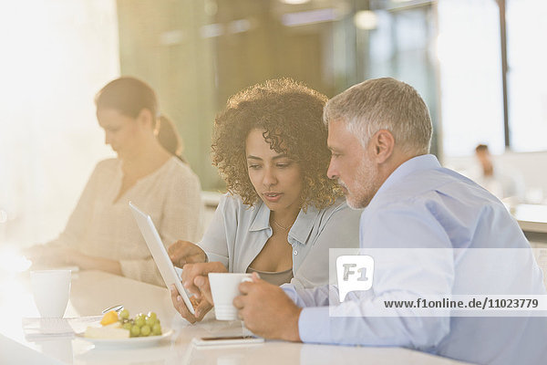 Business people drinking coffee and using digital tablet