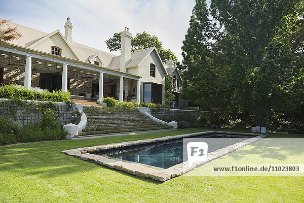 Home showcase exterior with swimming pool and tree