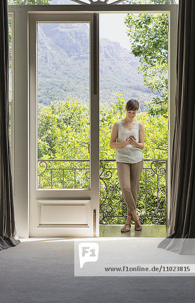 Woman texting with cell phone on luxury balcony