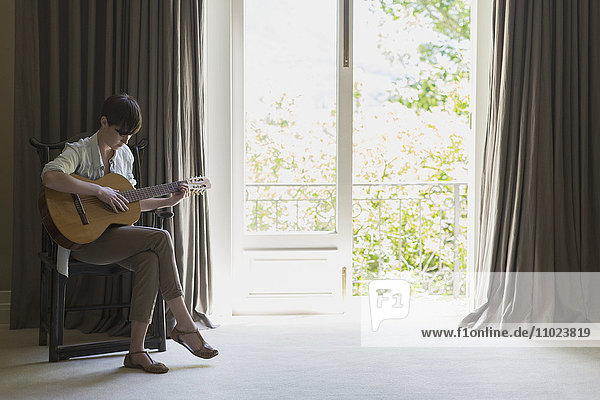 Woman playing guitar at balcony window