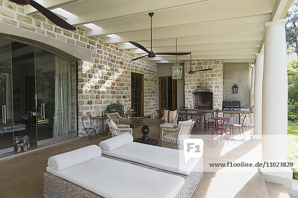 Luxury home showcase patio with stone wall and ceiling fans