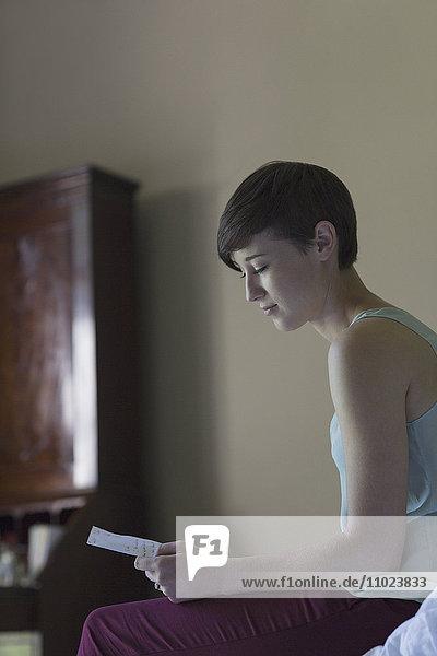Brunette woman reading letter in bedroom