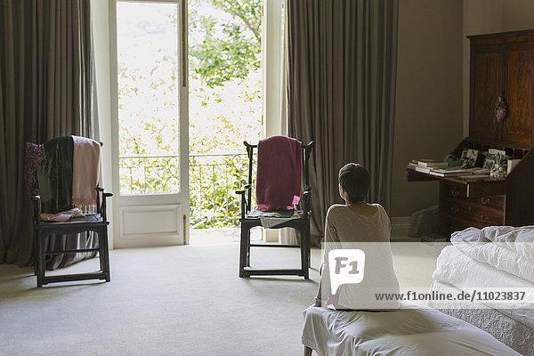 Woman looking out balcony window in luxury home showcase bedroom