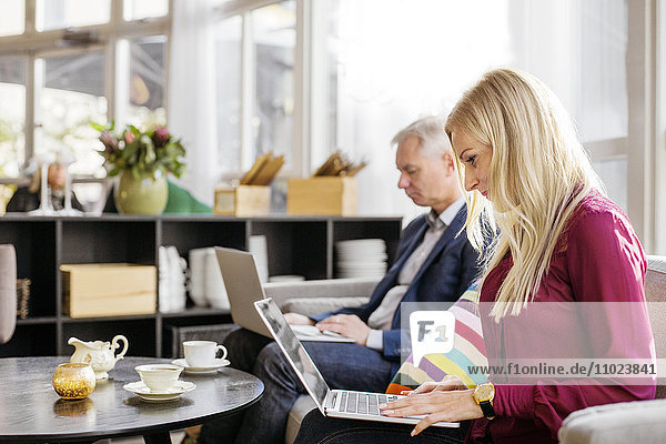 Business colleague using laptop in meeting at restaurant