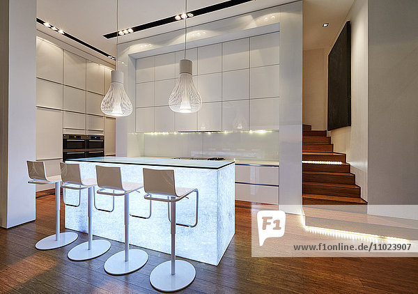 Illuminated modern luxury kitchen and staircase