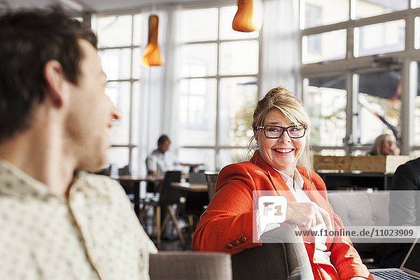 Happy business people discussing while sitting at restaurant