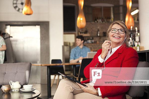Businesswoman talking through earphones while sitting at restaurant
